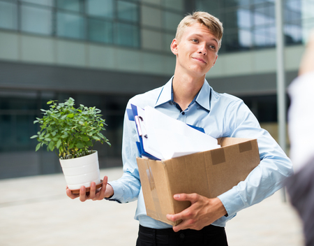 Businessman is standing pensive near office because he pending leave.