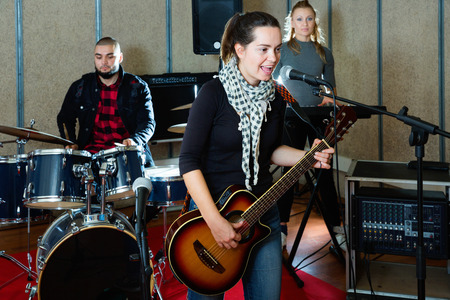 Attractive positive glad cheerful female soloist playing guitar and singing with her music band in sound studio