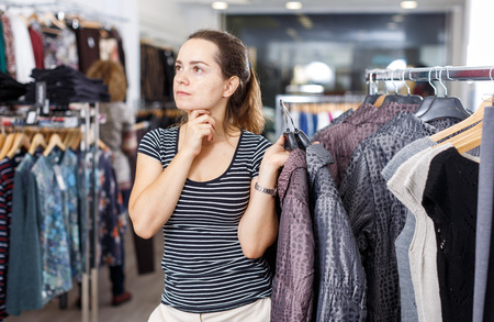 Young attractive woman choosing new overcoat in clothing store