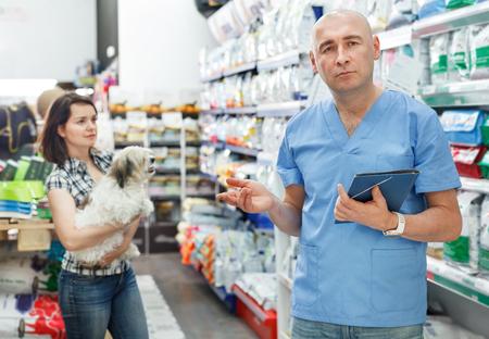 Veterinario hombre con carpeta de pie cerca de estantes con comida seca en una tienda de mascotas