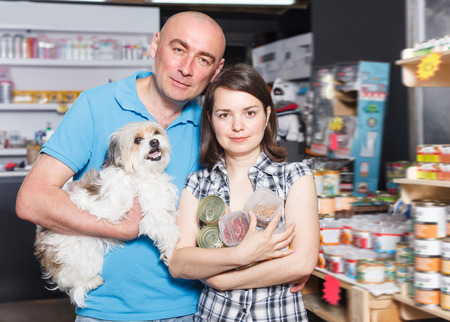 Portrait of young family couple with dog selecting vet  preserves in petshop