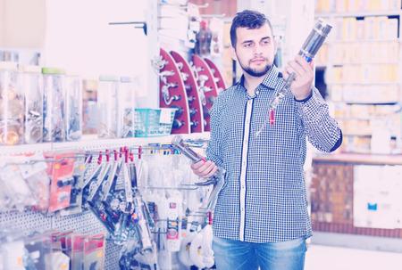 Young man customers choosing on best glue gun in houseware store