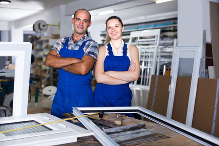 Portrait of male and female who are working at workshop for production of plastic windows.