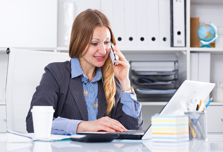 Successful business woman using phone and laptop at workplace