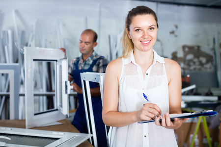 Young positive smiling woman manager standing with clipboard in workshop for production of plastic windows
