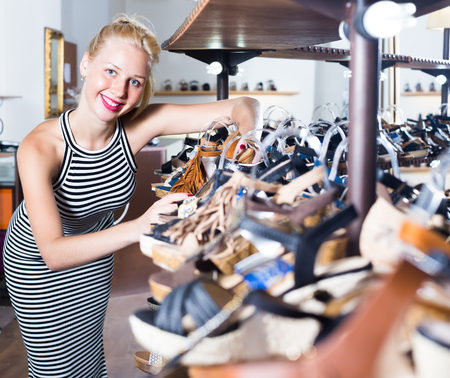 joyful smiling blonde girl in striped dress choosing pair of shoes in boutique Stockfoto - 123097856