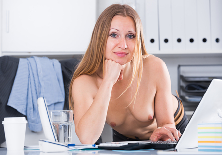 Sexy business lady dressed only in pants in office interior Imagens