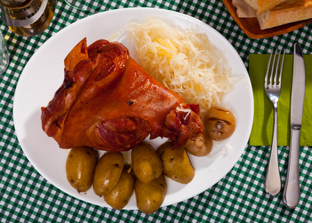 Plate of tasty baked pork knuckle with slices of baked potatoes and cabbage