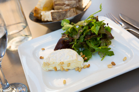 French dessert, cheese Saint Marcellin with pine nuts and fresh arugula 写真素材