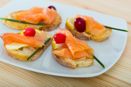 Mediterranean snack - bruschettes with salmon, butter and cranberries Stockfoto