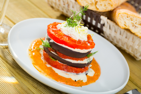 Dish  of  tasty fried eggplants with tomatoes on white and spicy sauce  at  plate