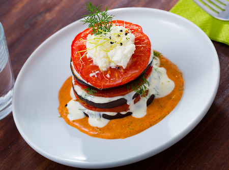 Top view dish of tasty eggplants with tomatoes on spicy sauce at white plate Stock Photo