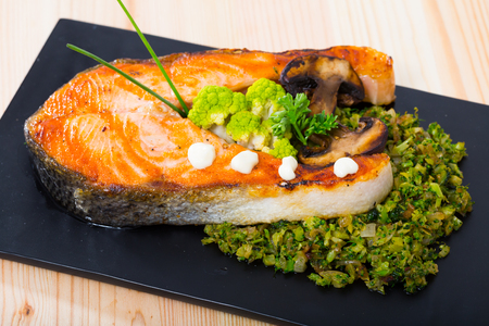 Grilled steak of salmon served with steamed broccoli and mushrooms on black serving board