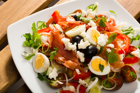 Traditional Shepherd's salad with salmon, fresh  tomato, cucumber and  quail eggs