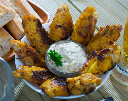 Grilled chicken wings with mustard sauce served in white bowl
