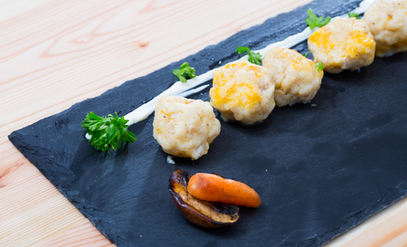 Image of dumplings of different white fish served with carrot at plate on table