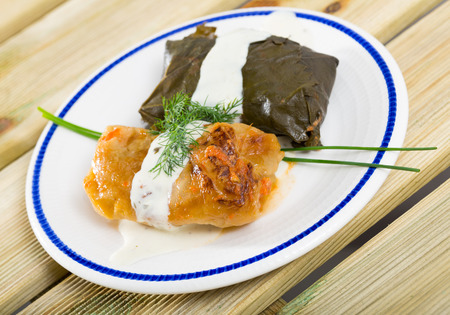 Tasty stuffed cabbage and grape leaves served with sour cream and fresh greens