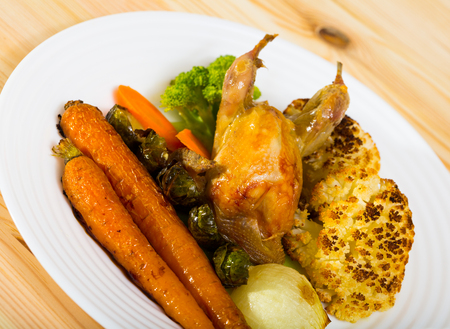 Grilled wildfowl with roasted vegetables in honey-mustard sauce served on white plate Imagens