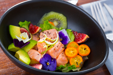 Exotic ceviche of salmon served with fresh avocado, cumquat, kiwi fruit, figs decorated with pansy flowers