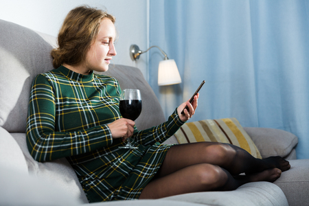 Young woman using smartphone while sitting with glass of wine on sofa 版權商用圖片