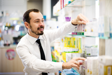 Smiling adult customer searching for reliable drug in pharmacy