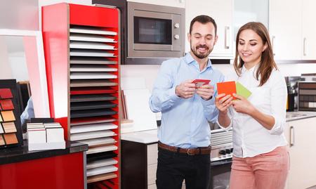 Married couple choosing stylish materials for kitchen furnishing in salon 版權商用圖片