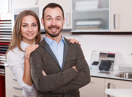 Pair of young positive people standing in furniture accessories shop