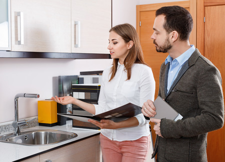 Polite cheerful  salesgirl helping young man in choice of mixer tap in kitchen furniture salon