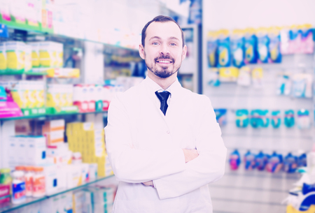 Happy male pharmacist displaying assortment of drugs in pharmacy Stockfoto