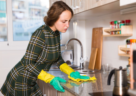 Positive housekeeper in rubber gloves cleaning kitchen furniture with rag