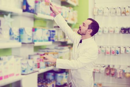 Farmacéutico hombre contento en busca de fármacos fiables en farmacia