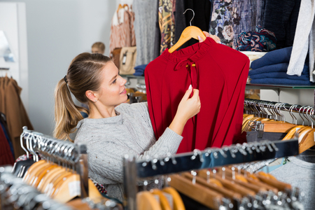 Portrait of positive girl holding red blouse on hanger in clothing shop Stock Photo