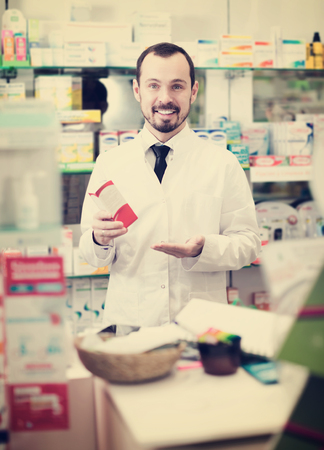 Smiling man medicine offer showing right drug in pharmacy Stockfoto