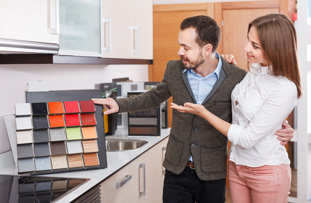 Young family couple choosing material for kitchen furniture in salon Stok Fotoğraf