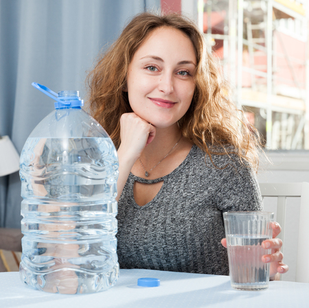 Young woman standing in living room and holding glass of pure water Reklamní fotografie
