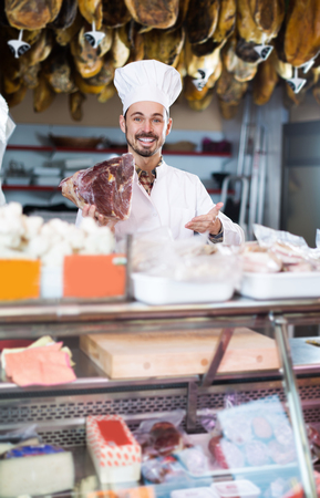 Smiling man seller showing piece of meat in butcher's store