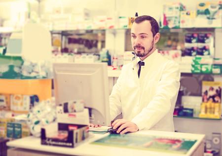 Smiling man pharmacist writing down assortment of drugs in pharmacy