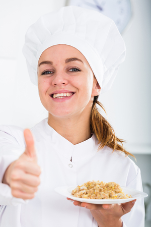 girl in chefs hat and white coat showing porrige at kitchen