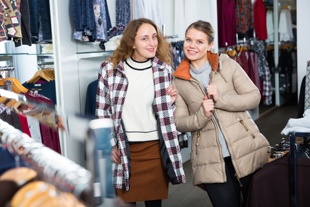 Portrait of two happy female friends posing in new coat in clothing showroom