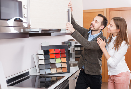 Young couple looking material for kitchen furniture in salon