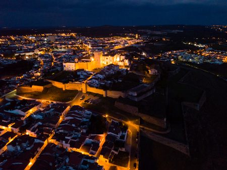 Aerial view of illuminated Castle of Estremoz with cityscape on background at night, Evora, Portugal