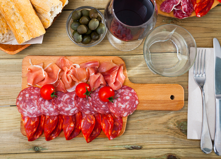 Traditional Spanish tapas - slicing sausages and jamon served on wooden board with cherry tomatoes Imagens