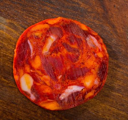 One slice of Spanish smoked pork sausage chorizo on wooden surface
