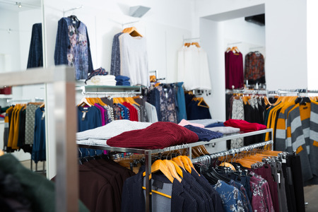 Various blouses and cardigans on hangers and shelfs in clothing shop interior