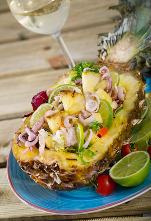 Exotic salad with squid, pineapple and lime dressed with sauce of pineapple juice, olive oil, lemon and chili pepper