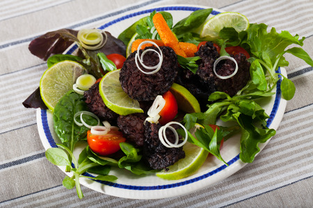 Traditional Spanish blood sausage with rice served with mix of greens, vegetables and lime Imagens