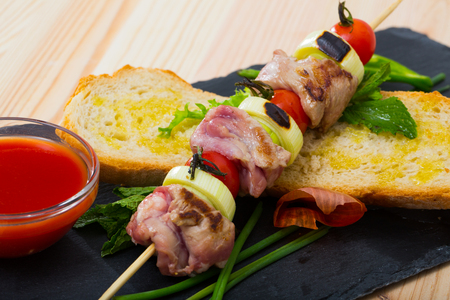 Appetizing shashlik of lamb meat pickled in red wine, khmeli-suneli and mint grilled on skewer with onion and tomatoes served with homemade ketchup Reklamní fotografie