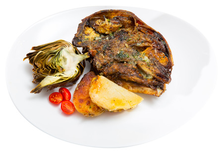 Delicious baked head of lamb served on white plate with roasted potatoes and artichoke. Isolated over white background