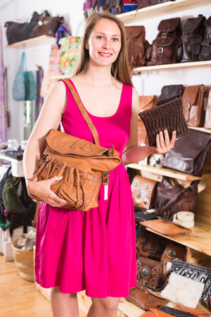 happy italian young blonde woman in shop chooses hand bags