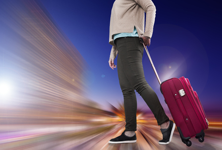 Traveler woman with suitcase awaiting landing aircraft on blurred background